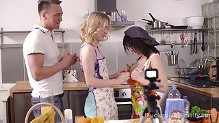 Several cooking girls in aprons swallow a big dick covered in whipped cream and get fucked